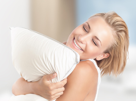 girl home: Happy girl enjoying white soft pillow, playing with downy cushion, closed eyes of pleasure, having fun at home, happy joyful youth lifestyle Stock Photo