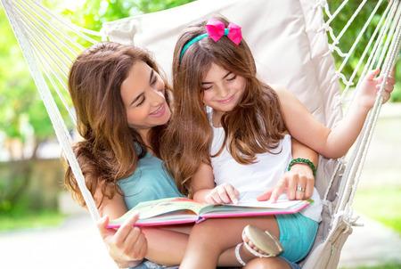 convivencia familiar: Retrato de la madre hermosa con la pequeña hija linda que se sienta en el patio trasero en hamaca y leyendo historia divertida, vida familiar feliz