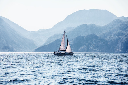 voyage: Beautiful sea landscape, sailboat sailing on the distance on great majestic mountains background, romantic cruise in the Mediterranean sea, beauty of Turkish nature