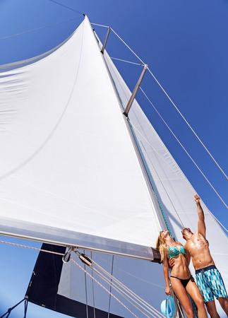 luna de miel: Feliz pareja joven alegre de pie en la cubierta del barco de vela y soñador mira para arriba en el cielo, disfrutando de las vacaciones de luna de miel, vacaciones románticas de verano