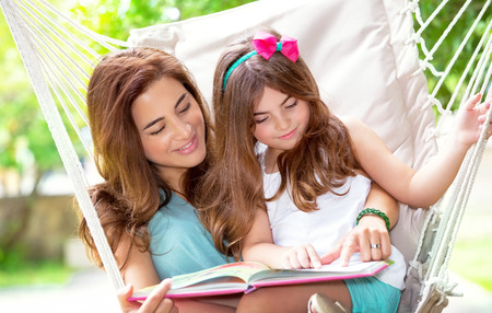 mum and daughter: Portrait of beautiful mother with cute little daughter sitting on backyard in hammock and reading interesting book, spending wonderful summer holidays together Stock Photo