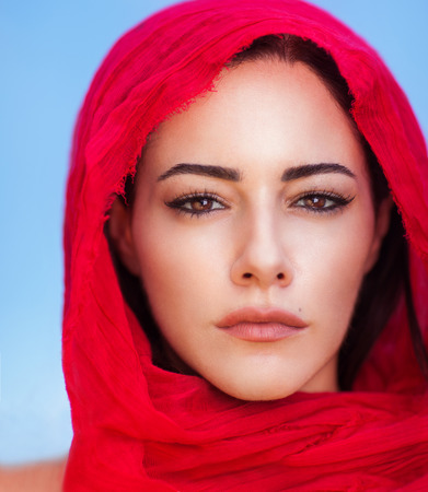 Primer retrato de la hermosa mujer árabe que lleva pañuelo rojo sobre fondo de cielo azul, maquillaje natural perfecto, belleza árabe tradicional
