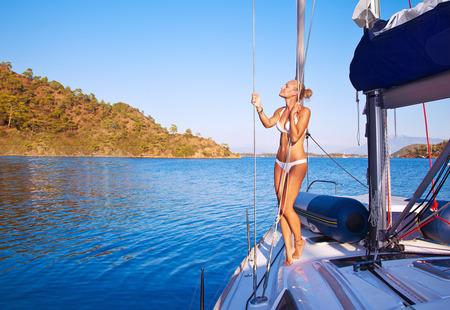 calor: Mujer atractiva en velero, muchacha bonita con el bronceado cuerpo perfecto en la cubierta de transporte de agua, vacaciones en la playa activa, disfrutando de las vacaciones de verano