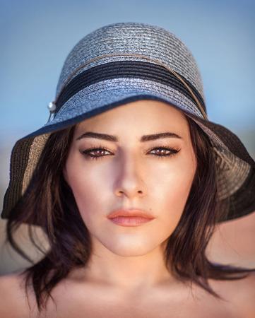 Closeup portrait of beautiful arabic woman wearing stylish sun hat, gorgeous female with perfect makeup outdoors photo