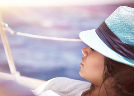 sailboat: Beautiful woman relaxing on the deck of sailboat in sunny day and tanning, enjoying peaceful luxury summer vacation on a sea cruise Stock Photo