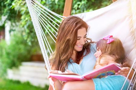Vrolijke moeder met baby dochter plezier buitenshuis, ontspannen in een hangmat en het lezen grappig verhaal, gelukkig gezin tijd doorbrengen op het platteland Stockfoto