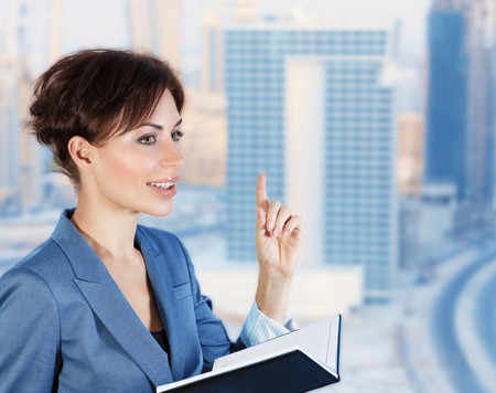 vp: Beautiful business woman in an office with windows overlooking the luxurious new buildings, holds a meeting with colleagues, successful career of young people Stock Photo