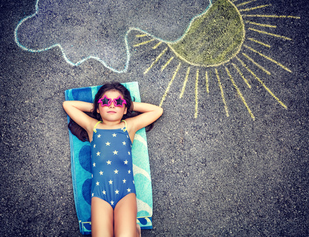 Happy little girl wearing swimsuit and lying down on the asphalt near picture of the sun comes out from behind the clouds, cute baby needs of summer holidays