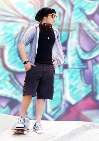 escucha activa: Chico del skate con estilo la m�sica que escucha permanente al aire libre en el hermoso fondo de la pintada de la pared, la vida adolescente activa, estilo inconformista, estilo de vida de la moda Foto de archivo