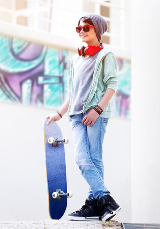 Cute teen boy with skateboard outdoors, standing on the street with different colorful graffiti on the walls, hipster style, cool teen fashion