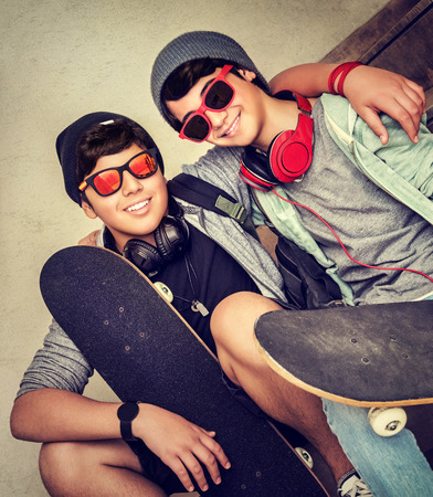 Two happy stylish teen boys sitting on the bench and holding skateboards, cheerful active friends enjoying outdoors sport, fashion teenagers lifestyle