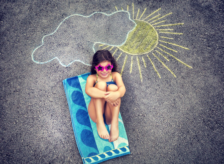 Cute creative little girl drawing on asphalt sun and tanning under it, wearing stylish swimsuit and sunglasses, summer holidays in the city Фото со стока