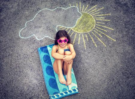 toallas: Linda creativa niña dibujo sobre asfalto sol y el bronceado bajo ella, vistiendo traje de baño con estilo y gafas de sol, vacaciones de verano en la ciudad Foto de archivo