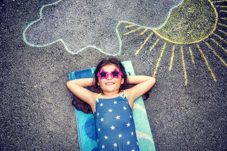 Gelukkig meisje dat zwempak draagt en stijlvolle zonnebril liggend op het asfalt in de buurt beeld van de zon komt van achter de wolken, schattige baby behoeften van de zomervakantie