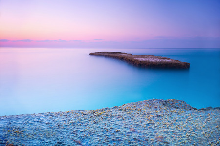SEA  LANDSCAPE: Beautiful blue and pink sunset over sea, amazing landscape of rock coast, wonderful destination for summer romantic vacation Stock Photo