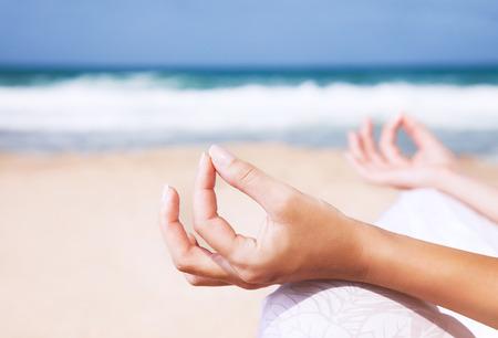 Vrouw, zittend op het strand in lotusbloem stelt en mediteren, lichaamsdeel, doet yoga oefening buitenshuis, zen evenwicht en ontspanning concept