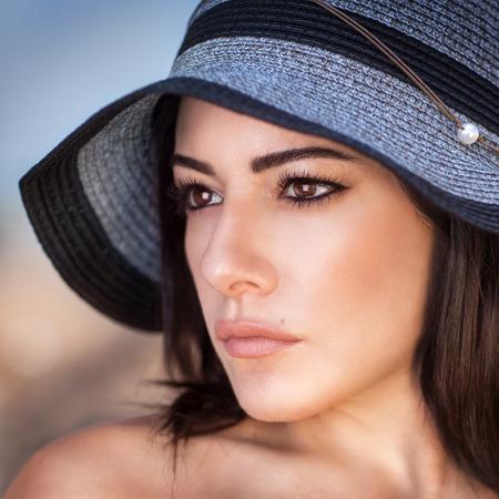 Closeup portrait of beautiful gorgeous woman wearing stylish sun hat, perfect makeup, seriously looking on a side, fashion and beauty photo