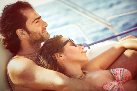 recreation yachts: Peaceful couple relaxing on sailboat, lying down on the deck and enjoying tranquil summer trip on water transport, pleasure and enjoyment from romantic relationship Stock Photo