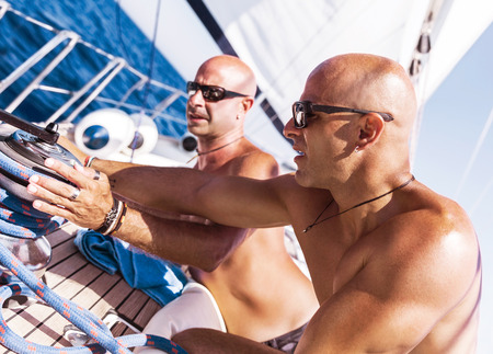 skipper: Two handsome shirtless sailors working on sailboat, involved in maritime competition, enjoying water sport, active summer vacation