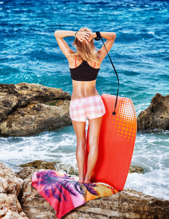 water sports: Woman enjoying beach activity, back side of sexy slim female standing on rocky coast with surf board, engage in water sports, active summer vacation