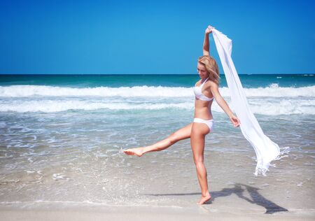 scarf beach: Beautiful woman dancing on the beach wearing stylish swimsuit and holding white scarf, relaxation outdoors on tropical resort, enjoying freedom and summer vacation