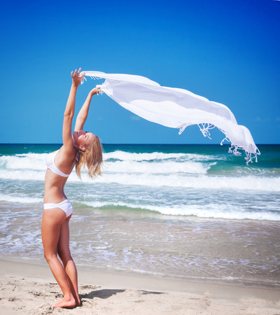 scarf beach: Beautiful woman on the beach, sexy slim model with raised up hands holding white scarf fluttering in the wind, happy summer vacation Stock Photo