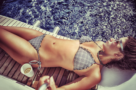 hot girl lying: Beautiful woman on beach holidays, gorgeous model with perfect body lying down on the board of sailboat and tanning, enjoying luxury summer vacation