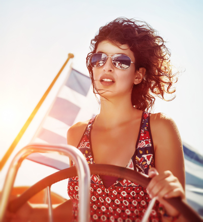 sailboat: Beautiful woman driving sailboat, steering wheel in mild yellow sunset light, enjoying water travel in the evening, active summer vacation