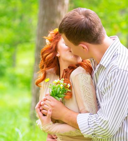baiser amoureux: Bonne jeune couple amoureux embrassant l'extérieur, fille reçoit un bouquet de fleurs de son petit ami, la première affection, relation amoureuse