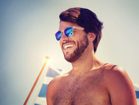 flag background: Portrait of handsome cheerful man over blue sky background, traveling on water transport with the Greek flag on board, happy beach holidays