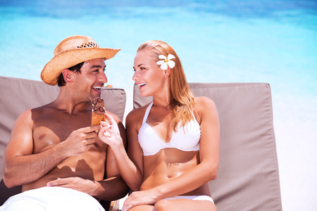 guy on beach: Happy couple on the beach sitting on sunbed and eating tasty sweet ice cream, with love looking on each other, enjoying romantic summer vacation