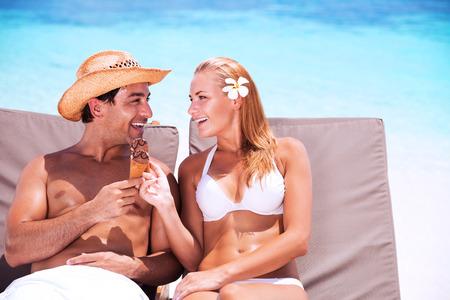 romantyczny: Szczęśliwa para na plaży siedzi na leżaku i jedzenie smaczne słodkie lody, z miłością patrzy na siebie, ciesząc romantycznych wakacjach