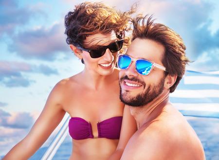 amantes: Retrato de feliz alegre linda pareja se divierte en el yate, disfrutando de unos a otros en el romántico viaje de verano, pasar la luna de miel en el mar