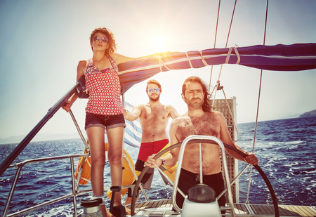Three friends on sailboat, enjoying summer holidays in the sea, active lifestyle, happy summertime adventure on water transport