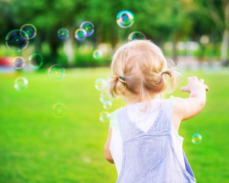 Kis kislány megpróbálja elkapni szappanbuborékok, szórakozás a szabadban, játék a parkban, boldog gondtalan gyermekkor