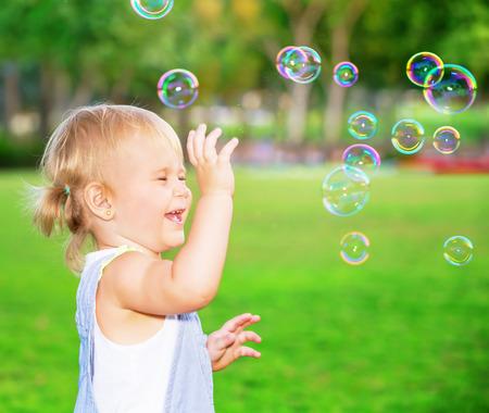 Gelukkig kind plezier in het park, schattige blonde meisje spelen met zeepbellen op de werf, vrolijk klein kind genieten van buiten spel Stockfoto