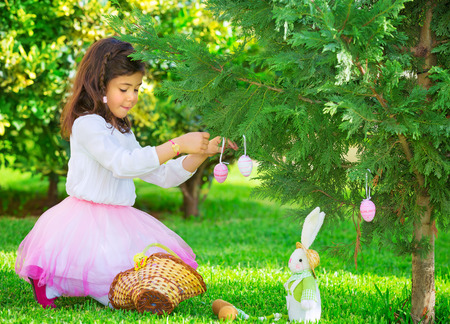Adorable little girl having fun outdoors with Easter bunny toy, decorated fresh green tree with coloring eggs, Happy Easter holiday Stockfoto