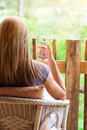 tomando agua: Mujer tranquila relajarse al aire libre, reverso de la mujer sentada en la silla en la terraza, agua potable y disfrutar de hermosas vistas naturaleza