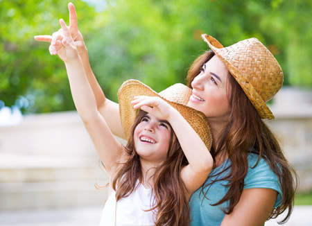 enthusiastically: Happy mother and daughter spending time together outdoors, pointing fingers and enthusiastically looking up, with pleasure spending time in countryside