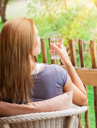 acqua bicchiere: Calm female sitting on the chair on balcony with water glass in hand, organic nutrition, healthy lifestyle, enjoying peaceful vacation Archivio Fotografico