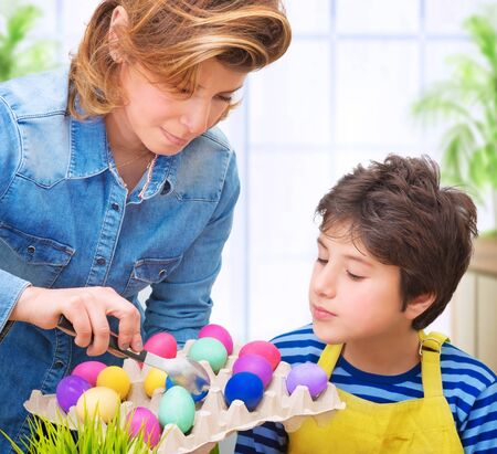 holiday tradition: Mother teach her cute son to paint eggs for Easter holiday, having fun at home and with pleasure coloring eggs, happy family tradition