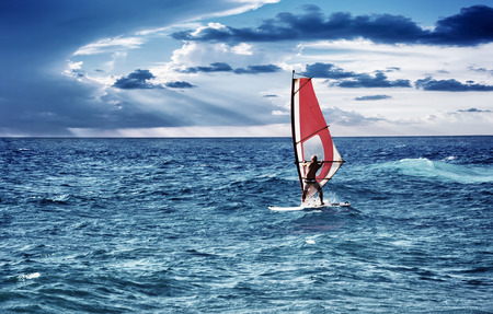 active: Windsurfer in the sea, man on windsurf conquering the waves, enjoying extreme sport, active lifestyle, happy summer vacation Stock Photo