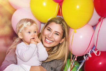 surprise party: Birthday party of baby girl, cheerful little child with mother having fun outdoors with many colorful balloons, happy family life Stock Photo
