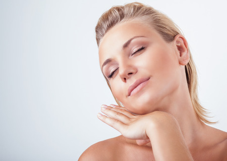 Portrait of gentle calm girl with closed eyes and hand near face over light background, natural skin care, perfect complexion, enjoying day spa Banco de Imagens