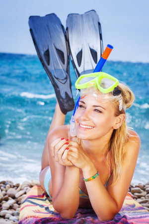 woman diving: Happy woman on the beach, wearing snorkeling equipment lying down on the seashore, pretty girl is interested in water sports, active summer vacation Stock Photo