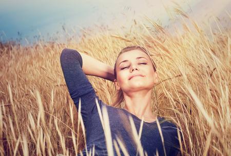 Leuk dromerig meisje op gouden rijpe tarweveld, liggend met gesloten ogen en geniet van prachtige zachte zonsondergang licht en in de herfst de natuur Stockfoto