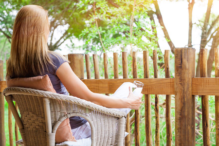 Back side of young woman sitting on armchair, drinking water and enjoying beautiful nature view, relaxing on the terrace, calm peaceful summer vacation
