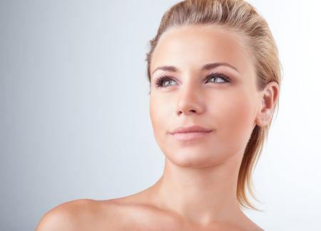 красота: Крупным планом портрет красивой нежной блондинка с естественный макияж светлом фоне, лицо уход за кожей, наслаждаясь спа-центр