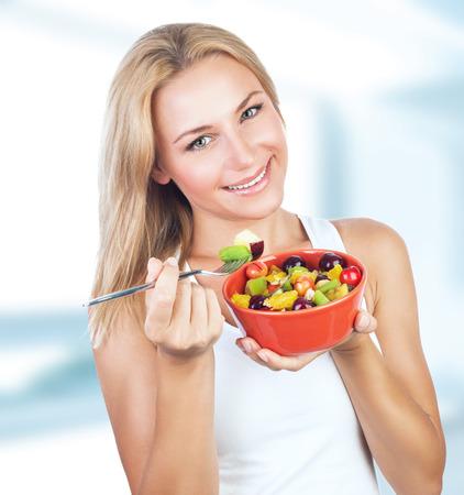 ensalada de frutas: Retrato de la hermosa mujer de comer sabroso ensalada de frutas para el desayuno en casa, estilo de vida saludable, el cuidado del cuerpo, la nutrición orgánica y concepto de dieta