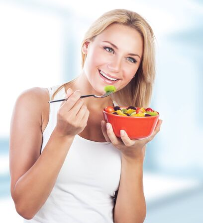 nutrition: Portrait of pretty blond woman eating fresh tasty fruit salad on the kitchen at home, special fruity diet, enjoying organic nutrition and healthy lifestyle